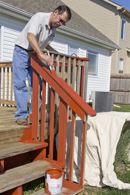 painter staining a deck in Oshawa
